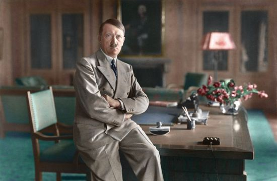 Hitler sitting on desk in the Berghof, color