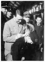 Hitler signing autograph on back of Hitler Youth boy