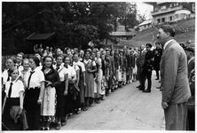 Hitler greeting a line of young women visitors at the Berghof driveway