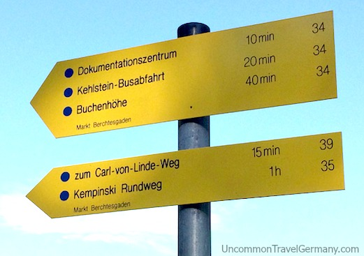 Yellow sign with nearby points of interest, near path to Berghof