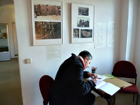 Man signing visitors' book at Colditz Castle