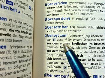 Pen pointing to translation of ubersetzen in German English dictionary