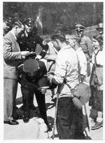 Hitler signing autograph on back of SS man